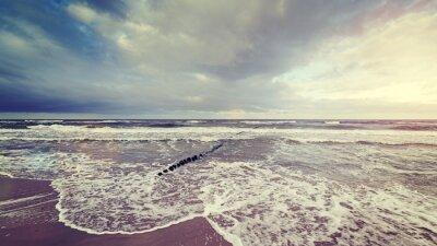 Fototapet Tappning tonad stormig himmel över grov sjö.