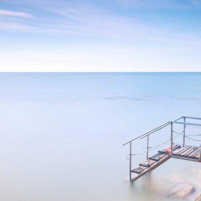 Fototapet Trä stege brygga till havsvatten. Lång exponering.