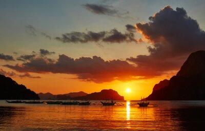 Fototapet Traditionella Filippino båtar på El Nido bay i solnedgång ljus.