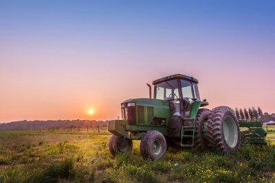 Fototapet Traktor i ett fält på en Maryland gård vid solnedgången