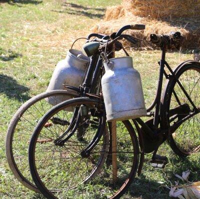 Fototapet två gamla rostiga cyklar för transport av mjölk i soporna