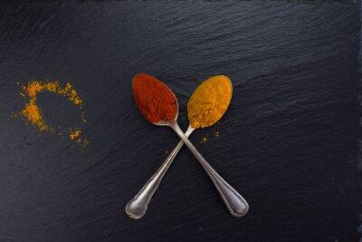 Fototapet Två vintage skedar med kryddor curry och paprika på svart bakgrund.