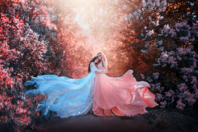 Fototapet two women in long dresses hugging train flies wind. bright fabulous purple colors art retouching processing. Natural cosmetics scented spring flowers tenderness smell perfume. Blonde brunette hair