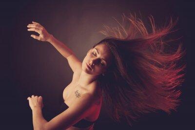 Fototapet Ung brunett kaukasiska kvinna dans och hennes hår flyter genom luften