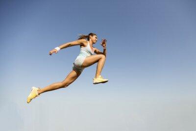 Fototapet Ung kvinna tar längdhopp