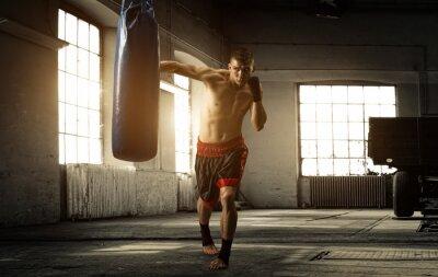 Fototapet Ung man boxning träningspass i en gammal byggnad
