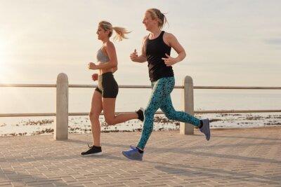 Fototapet Unga kvinnor som kör längs en strandpromenad