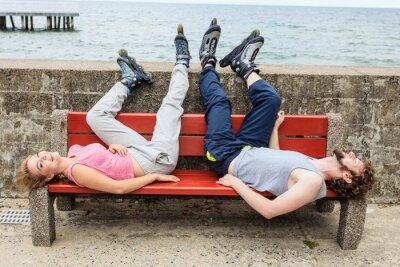 Fototapet Ungdomar vänner avkopplande på bänken.