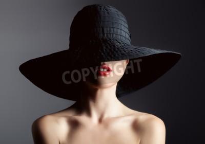 Fototapet Vacker kvinna i hatt. Retro mode. Mörk bakgrund.