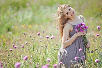 Fototapet Vacker kvinna med bukett i en blommor fält