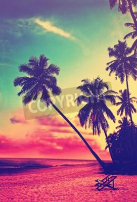 Fototapet Vacker tropisk strand med silhuetter av palmer i solnedgången