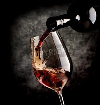 Fototapet Vin hälla i vinglas på en svart bakgrund