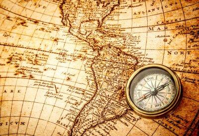 Fototapet Vintage kompass ligger på en gammal världskarta.