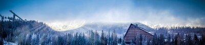Fototapet vinter natursköna panoramautsikt över berg med ett hotell och backhoppning plattform, sol täckt av moln
