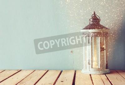 Fototapet vit trä tappning lykta med brinnande ljus och trädgrenar på träbord. retro filtrerade bilden med glitter overlay