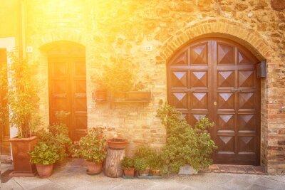 Fototapet Vy över den gamla gamla europeisk stad. Street of Pienza, Italien med trädörrar. Soliga bakgrund.