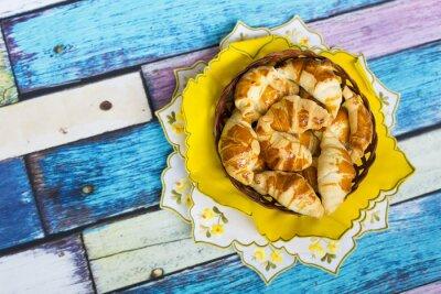Fototapet Самодельные круассаны в плетеной корзинке на желтой салфетке с цветочным узором на старом / вытертом полу