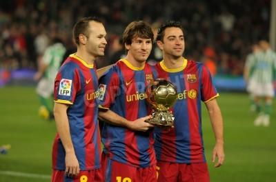Fototapet Iniesta, Messi och Xavi i Barcelona med gyllene bollen innan en spansk Cup-matchen mellan FC Barcelona och Real Betis på Camp Nou Stadium den 12 januari 2011 i Barcelona, Spanien