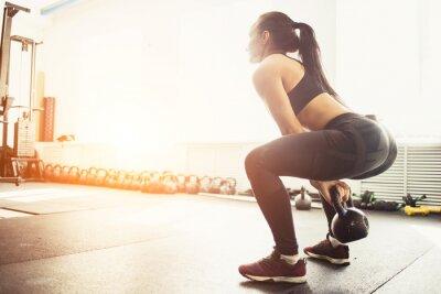 Väggdekor Athletic kvinna träna med kettlebell samtidigt som i squat position. Muskulös kvinna gör crossfit träning på gym.
