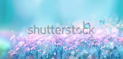 Väggdekor Blommigt naturligt landskap med vilda rosa lila blommor på äng och fladdrande fjärilar på bakgrund med blå himmel. Drömmande mild luftkonstnärlig bild. Mjukt fokus, författarbehandling.