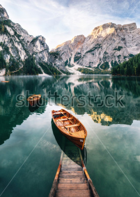 Väggdekor Boats and slip construction in Braies lake with crystal water in background of Seekofel mountain in Dolomites in morning, Italy Pragser Wildsee