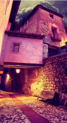 Väggdekor Calle de pueblo al Anochecer con Faroles y banco