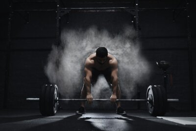 Väggdekor Crossfit athlete preparing to lift heavy barbell in a cloud of dust at the gym. Barbell magnesia protection.