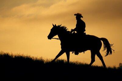 Väggdekor En silhuett av en cowboy och häst gå upp en äng med en orange och gul bakgrund himmel.
