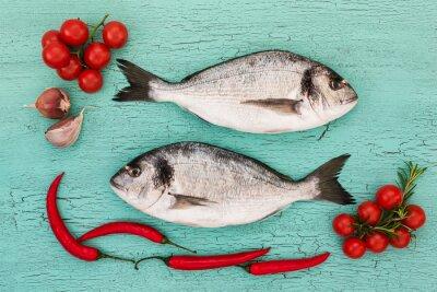 Väggdekor Färsk dorado fisk med grönsaker på blå bord. Kopia utrymme, ovanifrån