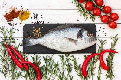 Väggdekor Färsk dorado fisk, rosmarin, körsbärstomater, kyliga peppar på vitt träbord. Toppvy.