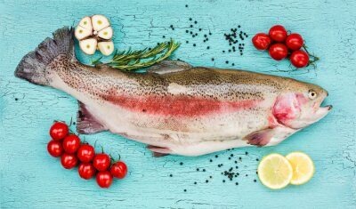 Väggdekor Färsk öring fisk med grönsaker på blå träbord. Toppvy