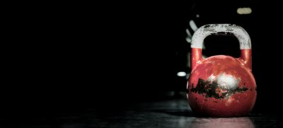 Väggdekor Heavy old used color kettlebell weight on the gym floor ready for fitness strength workout to build muscles with dark background and free copy space banner