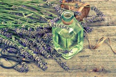 Väggdekor Herbal lavendelolja med färska blommor på trä bakgrund