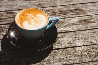 Väggdekor Kopp cappuccino med kaffe konst på träbord