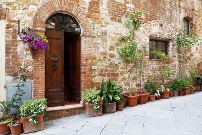 Väggdekor Kullerstensgatorna i de vackert dekorerade väggar med färgglada blommor, Toscana, Italien