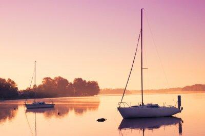 Väggdekor Lite segelbåtar återspeglar i den fridfulla vatten under soluppgången.