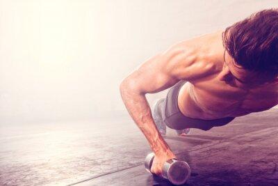 Väggdekor Man gör push-up träning med hantel. Stark man gör crossfit träning.