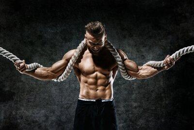 Väggdekor Muskulös man med rep. Foto av man med perfekt kropp efter träning. Mode