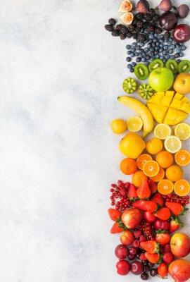 Väggdekor Rainbow fruits berries background on white. Top view of strawberries blueberries cherries mango apple lemons oranges red currants plums blackberries, selective focus