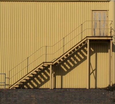 Väggdekor Trappor som leder över en metall sidinf vägg.