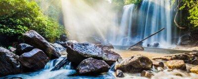 Väggdekor Tropisk vattenfall i djungeln med solstrålar