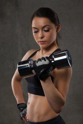 Väggdekor ung kvinna böja musklerna med hantlar i gymmet