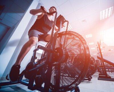 Väggdekor Unga män med muskulatur kropp med hjälp av flygcykel för kardio träning på korsträning.
