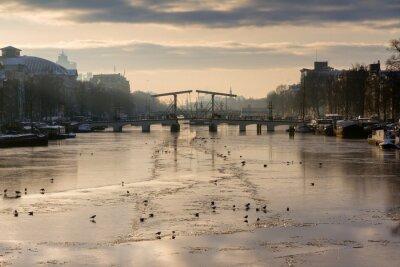 Väggdekor Vacker vinter panorama över floden Amstel i Amsterdam, Nederländerna, blicken mot den magra bron.