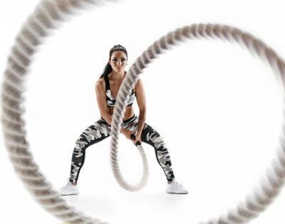 Väggdekor Woman doing exercises with battle rope. Photo of muscular model in military sportswear isolated on white background. Strength and motivation