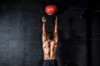 Väggdekor Young strong sweaty focused fit muscular man with big muscles doing throwing medicine ball up on the wall for training hard core workout in the gym real people selective focus