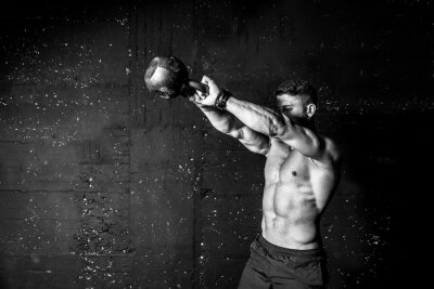Väggdekor Young strong sweaty focused fit muscular man with big muscles holding heavy kettle bell for swing cross training hard core workout in the gym black and white